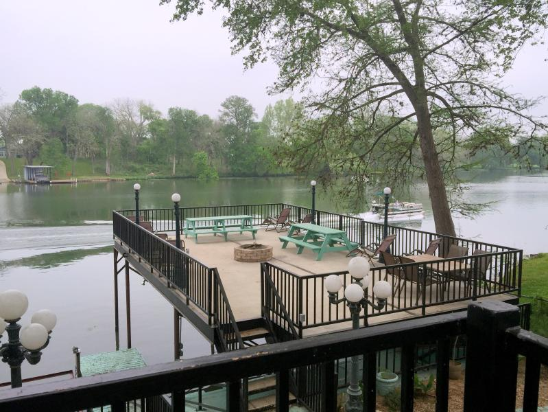 Scenic view from the cottage balcony of large upper deck and boaters on the river - GUADALUPE RIVER LODGE NEW BRAUNFELS HILL COUNTRY - New Braunfels - rentals